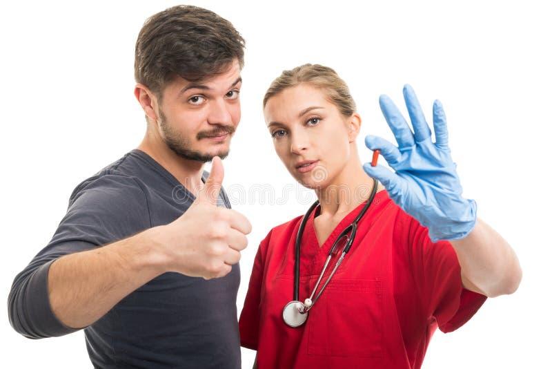 La demostración paciente masculina tiene gusto y doctor de sexo femenino que sostiene la píldora foto de archivo libre de regalías