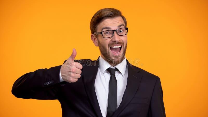 La demostraci?n sonriente del hombre de negocios manosea con los dedos para arriba en la c?mara, haciendo el buen asunto imagenes de archivo