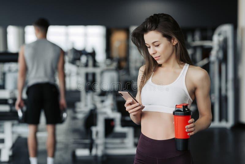La deportista joven hermosa en ropa de deportes y auriculares está sosteniendo una botella de agua, escuchando la música usando u foto de archivo