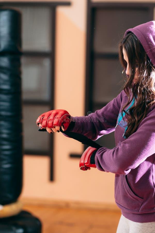 La deportista joven que envuelve las manos acerca al saco de arena fotografía de archivo libre de regalías
