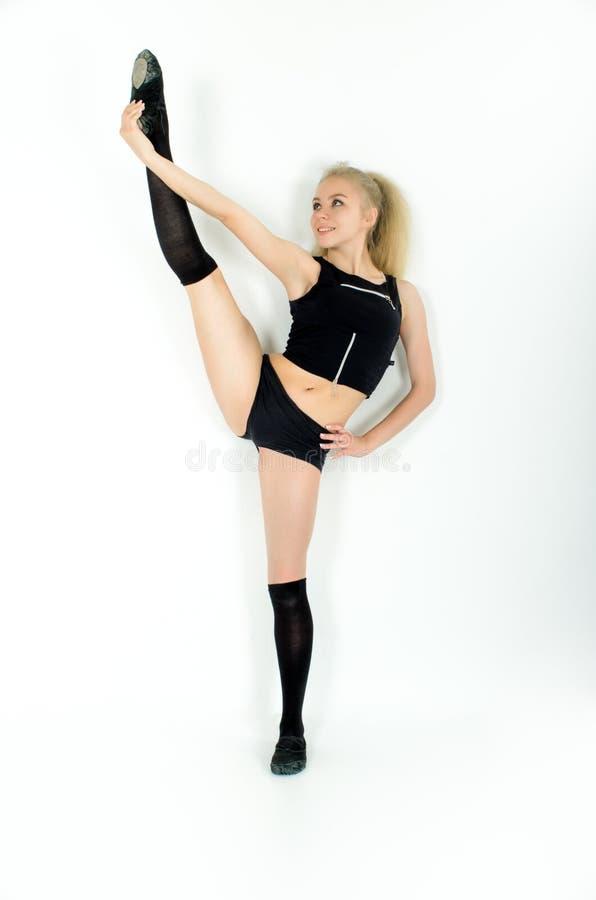 La deportista joven sonriente que hace estirar exorciza Aislado en el fondo blanco fotografía de archivo