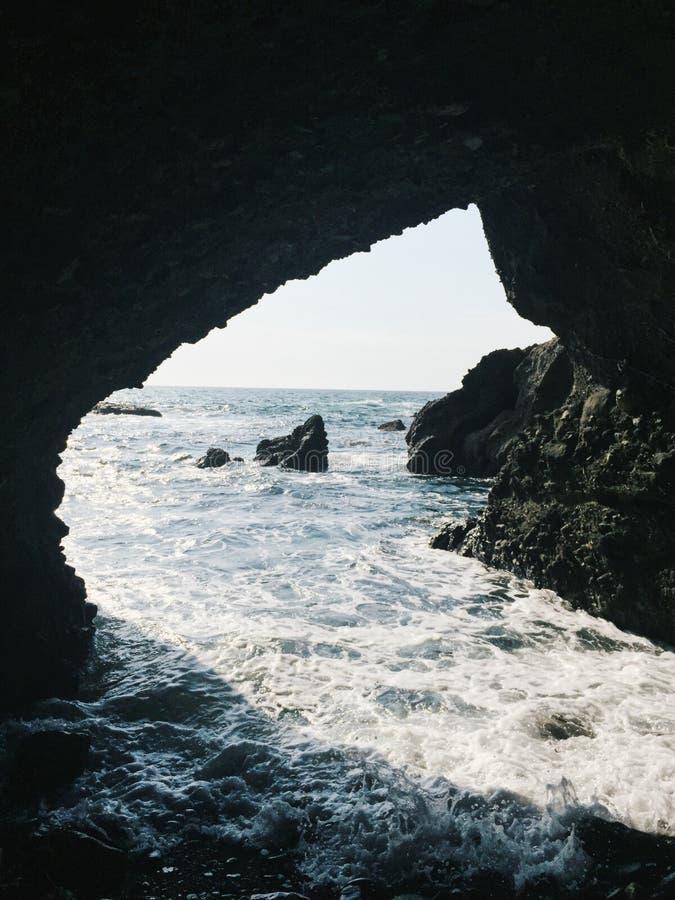 La derecha de la cueva en el océano imágenes de archivo libres de regalías