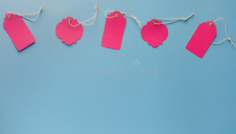 La derisione rosa in bianco dell'etichetta di vendita aumenta isolato su fondo blu con il co fotografia stock