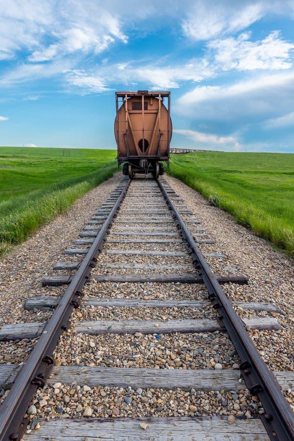 La dernière voiture de train dans une longue file avec la voie dans le premier plan en Saskatchewan rurale, Canada images stock