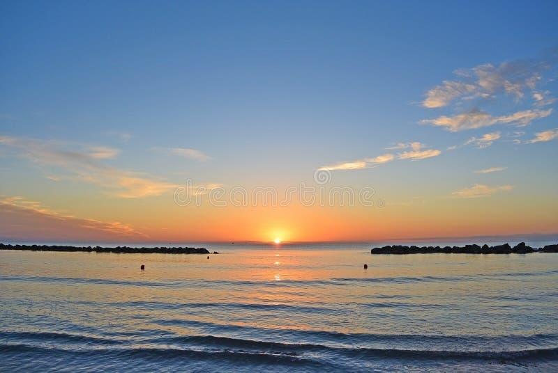 La descarga en la playa de la arena Cielo hermoso de la salida del sol sobre el mar imagen de archivo libre de regalías