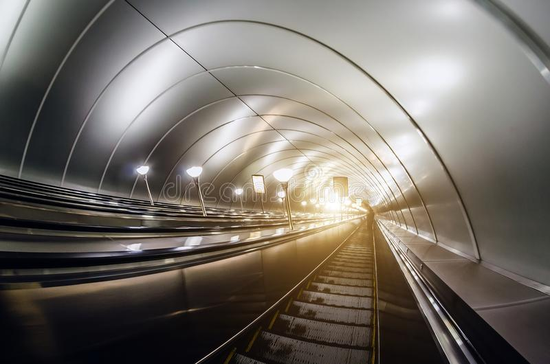 La descente dans les escaliers stéréo d'escalator de tunnel s'allument de dessous photo libre de droits