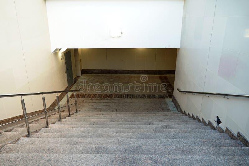 La descente moderne au tunnel piétonnier est vide sans personnes Escalier vers le bas au nouveau passage souterrain beige images stock