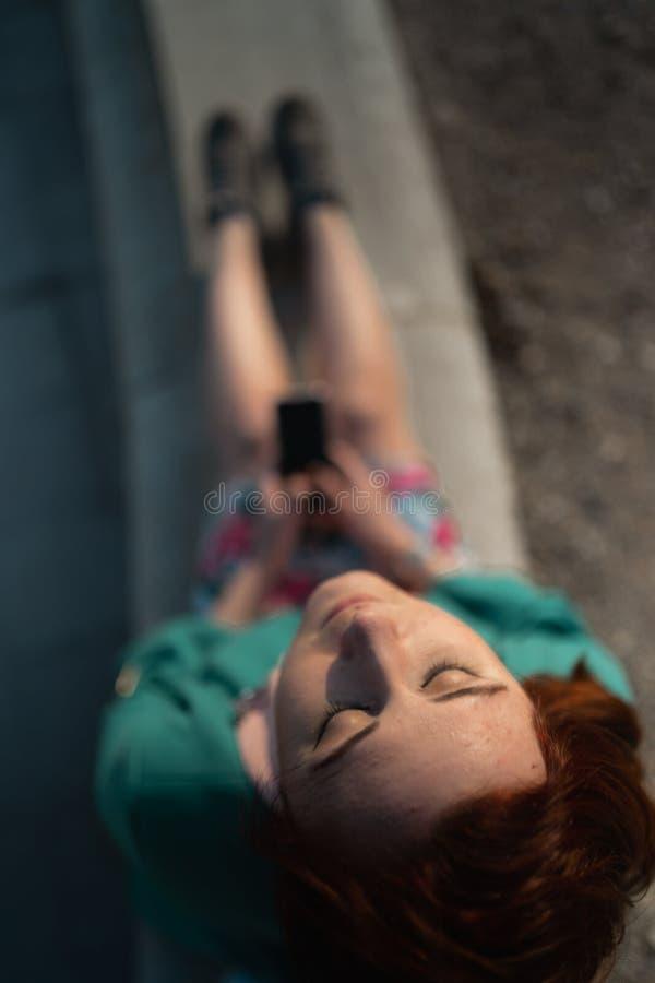 La descripción de una mujer joven utiliza el teléfono en un parque del palacio que se sienta en una fuente - visión desde arri imagenes de archivo