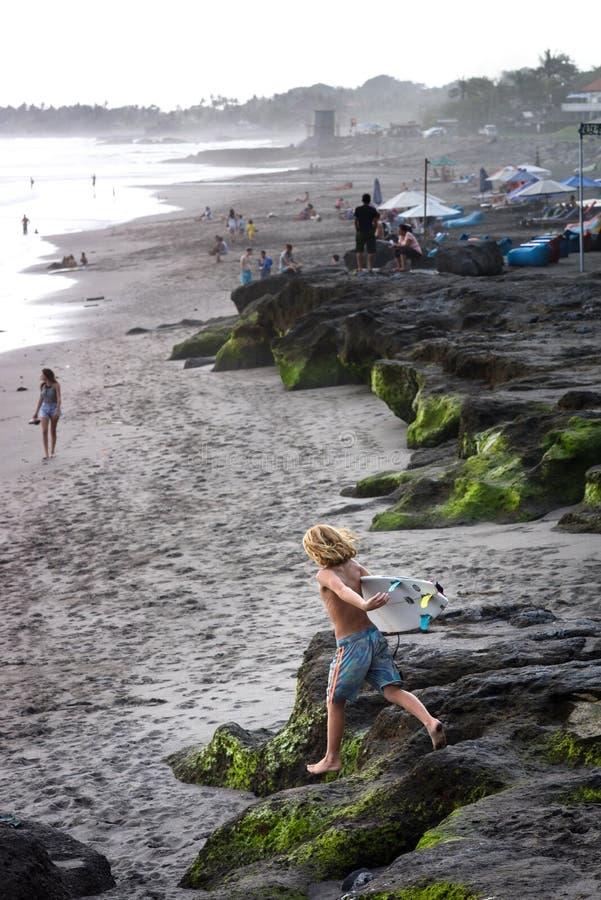 La destinazione di viaggio, scopre il paradiso praticante il surfing Giovane funzionamento del surfista del ragazzo verso la spia immagine stock