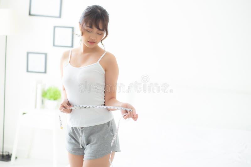La dieta asiática joven del cuerpo de la mujer y delgados hermosos con la cintura de medición para el peso en el dormitorio, much imágenes de archivo libres de regalías
