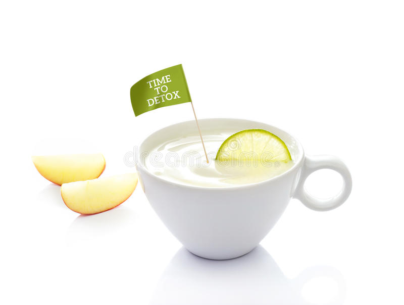La dieta del Detox, el yogur en taza con el limón y la bandera mandan un SMS a tiempo al detox en el fondo blanco imagen de archivo