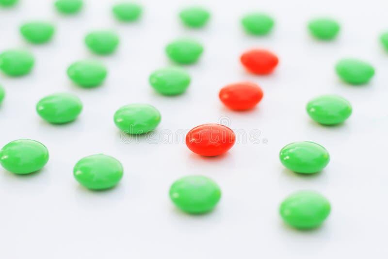 La diferencia hizo la dirección: gránulos rojos del pigmento en el verde imagen de archivo libre de regalías