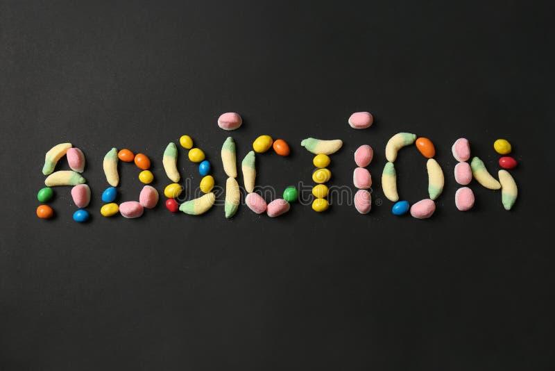 La DIPENDENZA di parola ha fatto con le caramelle su fondo scuro fotografie stock libere da diritti