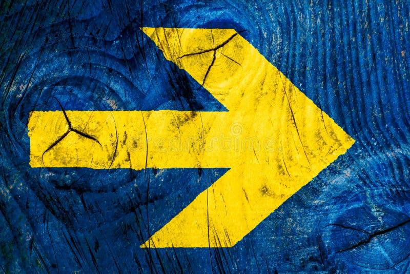 La direzione gialla della freccia cede firmando un documento la parete di legno di colore blu luminoso vivo con le imperfezioni e immagine stock libera da diritti