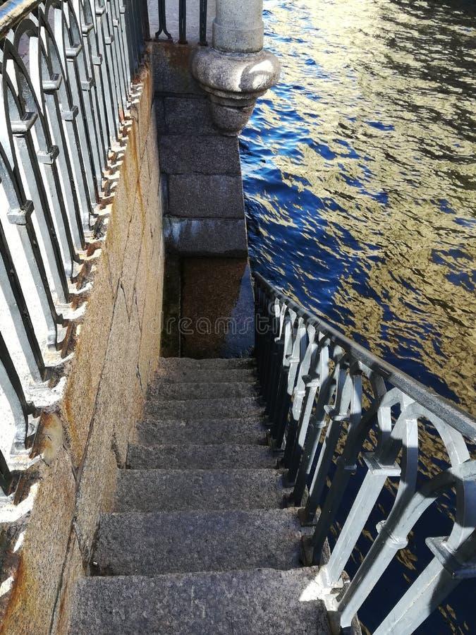La discesa all'acqua sulle scale del granito fotografia stock