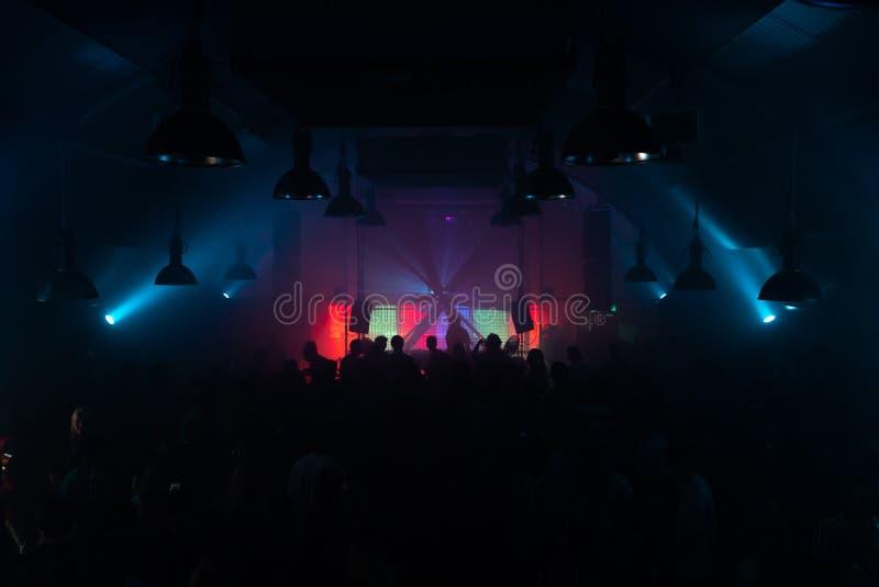 La discothèque Techno avec une foule en clubbing et un DJ derrière une table d'hôte images libres de droits