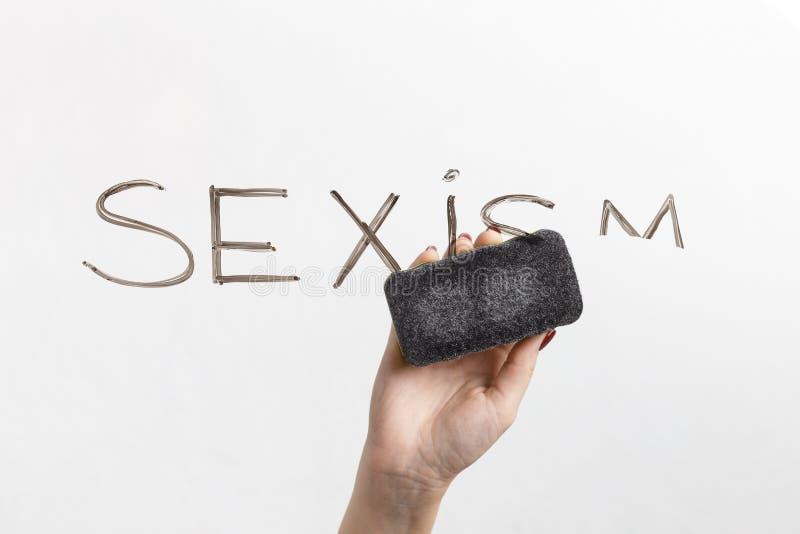 La discriminazione sessuale è scritta su vetro e sulla mano con la spugna fotografie stock libere da diritti