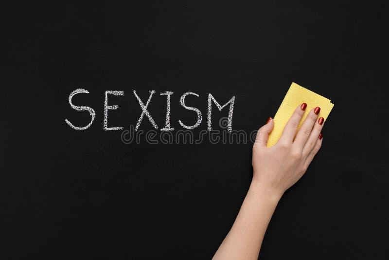La discriminazione sessuale è scritta sulla lavagna e sulla mano con la spugna immagine stock
