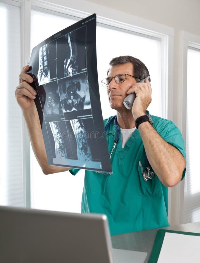la discussione del telefono paziente s del medico scandice spinale immagine stock libera da diritti