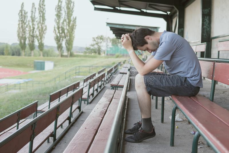 La disperazione e l'uomo depresso sta sedendosi nello stadio Concetto di solitudine ed isolato immagine stock