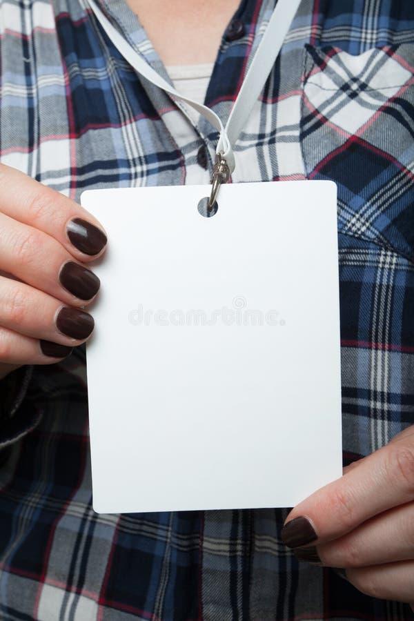 La disposición vertical es una marca nominal en las manos en el fondo de una camisa en una jaula Etiqueta de la identidad de la p imagen de archivo libre de regalías