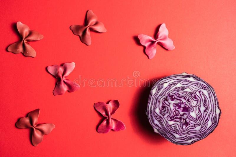 La disposition créative d'été faite en rose a coloré le chou et a coloré le papillon de semoule de pâtes sur le fond rose foncé l photographie stock libre de droits