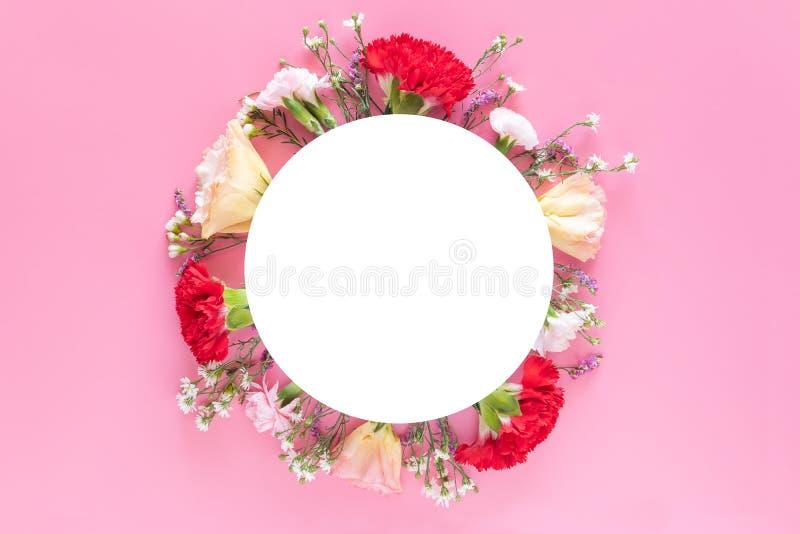 La disposition créative a fait avec les fleurs colorées fraîches de ressort sur le fond rose lumineux avec le label blanc de bann photos libres de droits