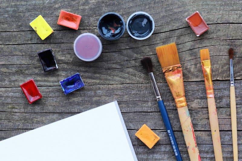 La disposition plate de l'acrylique et de l'aquarelle colorés peint, ensemble de brosses et bondit la moquerie blanche de feuille images libres de droits