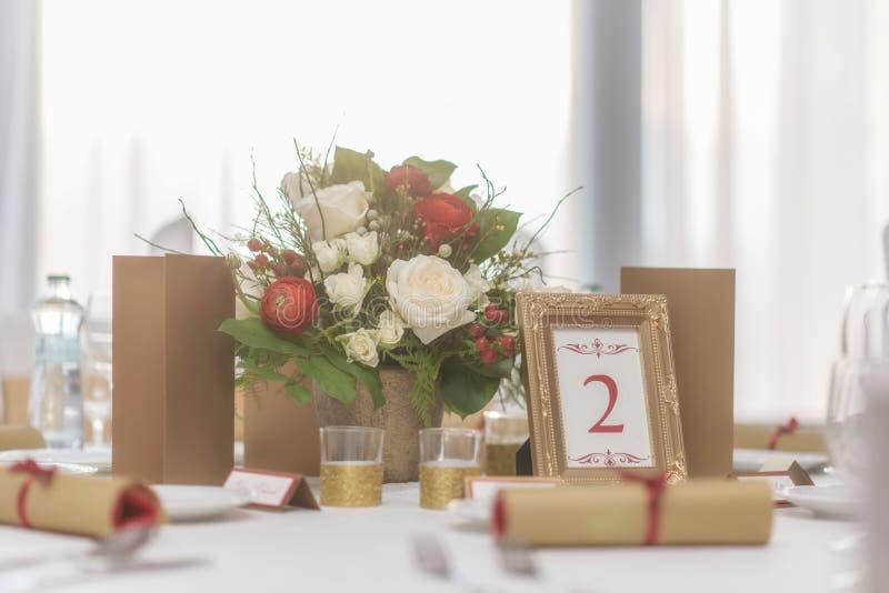 La disposizione floreale dell'avorio e rossa ha preparato per la ricezione, la tavola di nozze con la candela e la regolazione, c immagine stock