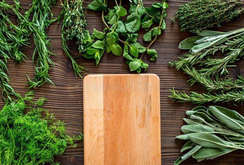La disposizione piana con le erbe e la pianta fresche per l'essiccamento e produrre delle spezie ha messo sul modello di legno de fotografie stock libere da diritti