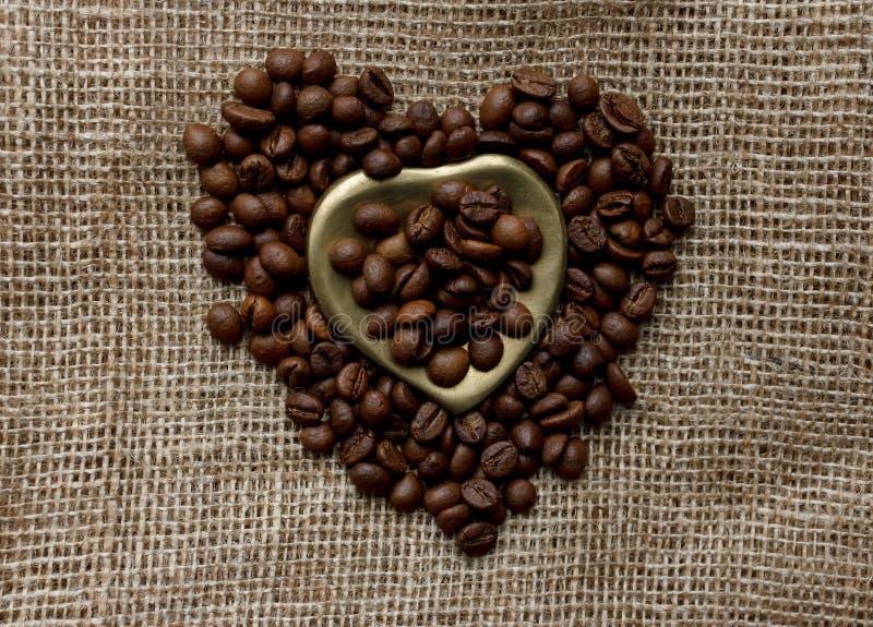 La disposizione piana dei chicchi di caffè arrostiti su una tovaglia con un cuore dorato ha modellato il piattino e la tazza da c fotografia stock libera da diritti