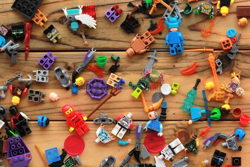 La disposizione piana dei giocattoli di Lego ha sparso sulla tavola di legno immagini stock