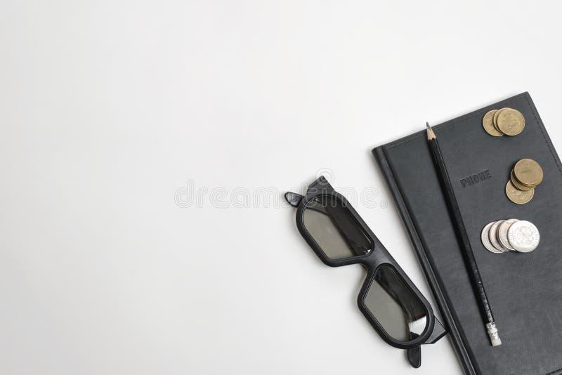 La disposizione piana del taccuino, della penna, dei vetri e della rublo neri conia su superficie di legno con lo spazio della co fotografia stock