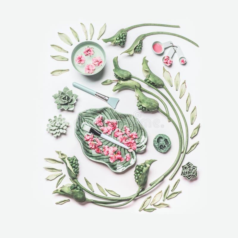La disposizione piana naturale di cura di pelle e della stazione termale con acqua lancia, fiori, foglie verdi, asciugamano ed ac fotografia stock libera da diritti