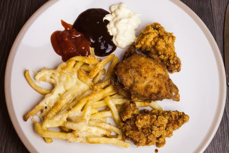 La disposizione piana sopra le patate fritte con le ali di pollo fritto e del formaggio con salsa è servito sul piatto bianco Imm fotografia stock