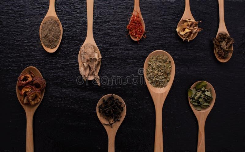 La diversa clase de hojas, de fruta y de flor secadas puso en muchos la clase de cucharas de madera en fondo negro con el espacio fotografía de archivo