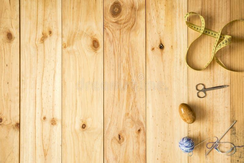 La diversa costura equipa, incluyendo las tijeras, cinta métrica, los hilos de las lanas y las agujas en fondo de madera ligero foto de archivo