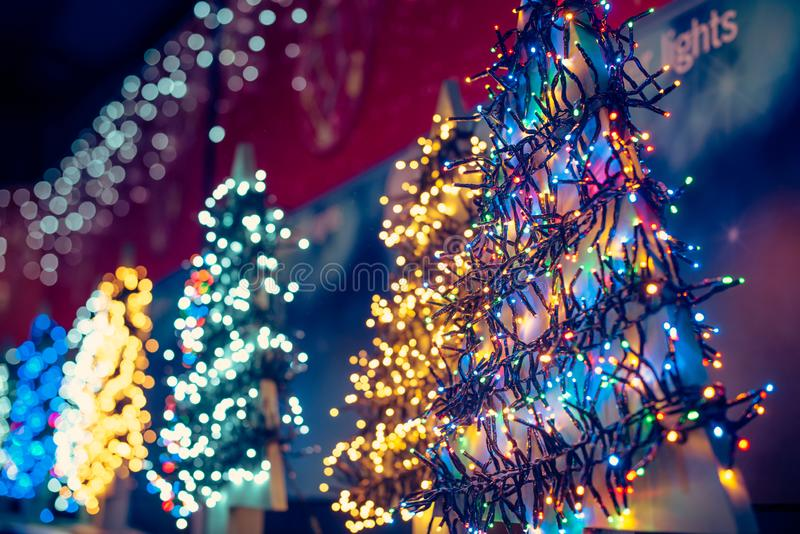 La diversa Navidad que brillaba intensamente colorida llevó las guirnaldas de las luces en la exhibición de la tienda Fondo del d fotografía de archivo