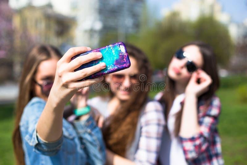 La diversión hawing de los adolescentes felices pasa el tiempo junto en el parque de la ciudad imagen de archivo