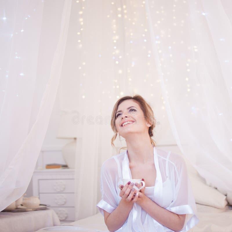 La diversión hermosa de la mujer ríe en el café de consumición del dormitorio Una muchacha sostiene la taza, disfruta de una bebi fotografía de archivo libre de regalías