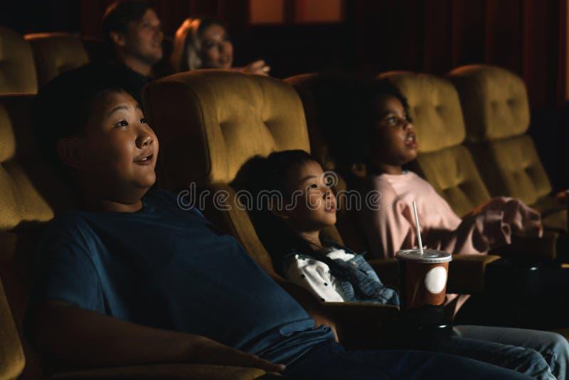 La diversità dei bambini e delle persone, di colore americano, caucasico e asiatico, si diverte a guardare il film al cinema immagine stock