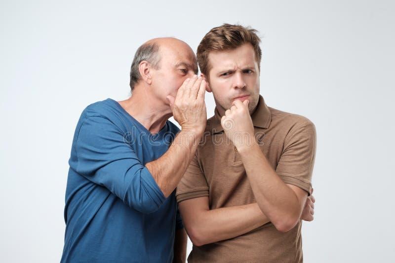 La divisione dell'uomo senior segreta o bisbigliare pettegola nel suo orecchio del figlio Dire concetto di segreto della famiglia fotografia stock libera da diritti