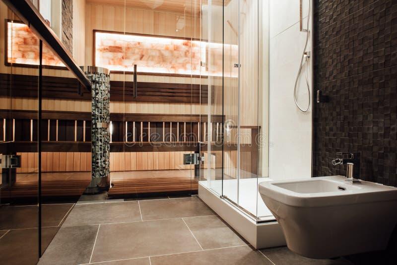 La doccia con un bidet, una doccia di vetro e una sauna dietro una porta di vetro immagine stock libera da diritti