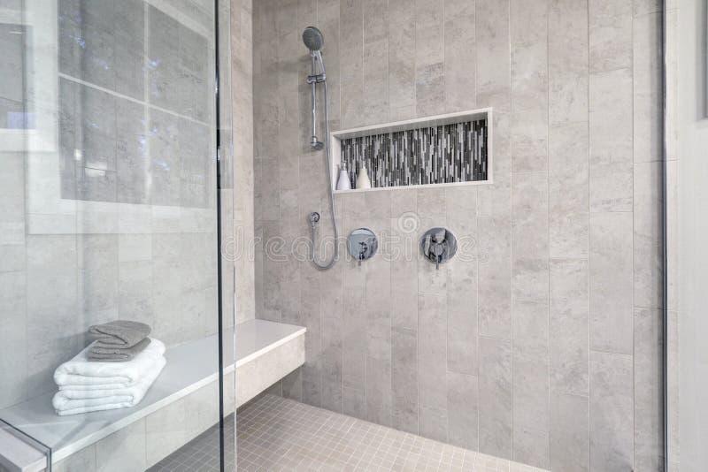 La doccia delle persone senza appuntamento di vetro in un bagno della casa nuovissima fotografia stock