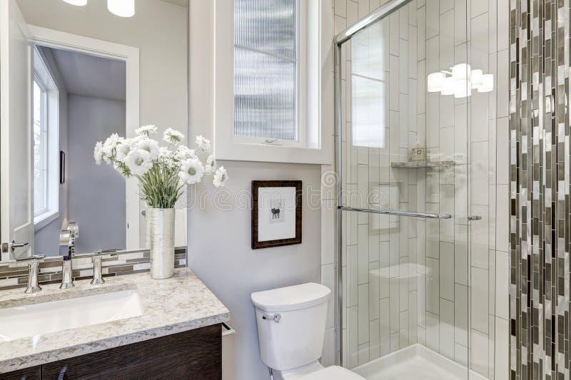 La doccia delle persone senza appuntamento di vetro in un bagno di nuova casa di lusso immagine stock
