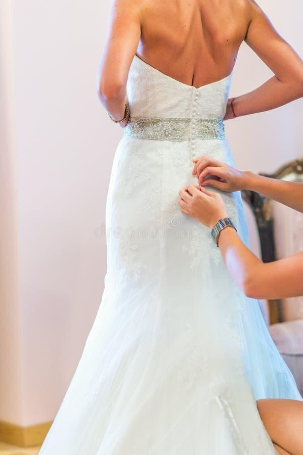 La domestica Buttoning della sposa il vestito da sposa immagini stock