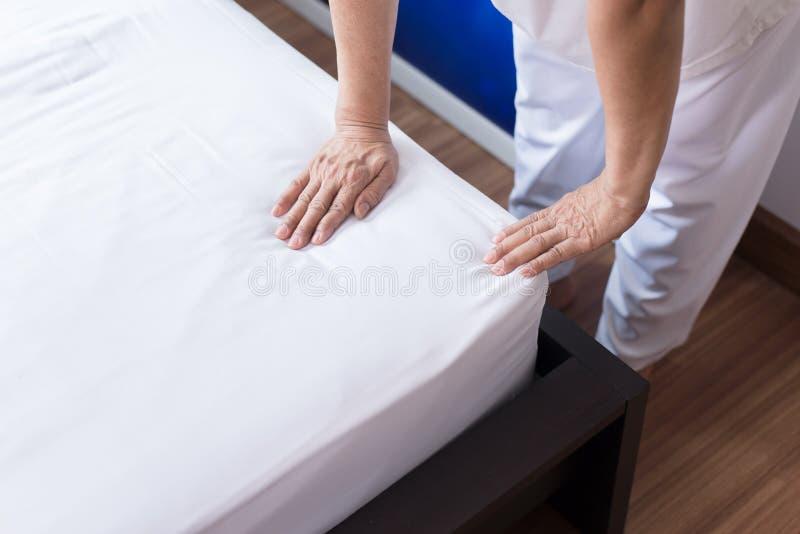 La domestica della donna che fa il suo letto bianco nella sala dopo sveglia, gli anziani femminili fa un letto fotografie stock