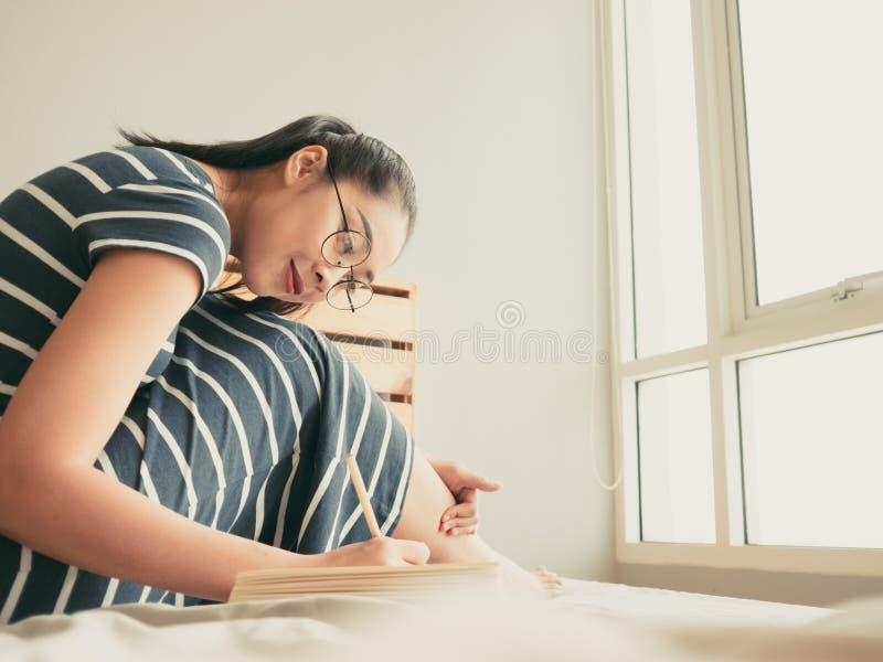 La donna è libro di lettura nella camera da letto fotografia stock libera da diritti