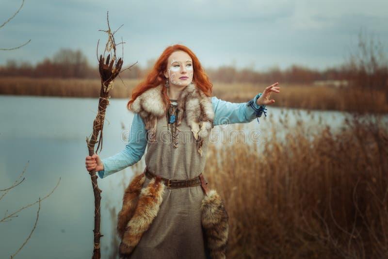 La donna è uno sciamano con un personale in sue mani fotografie stock