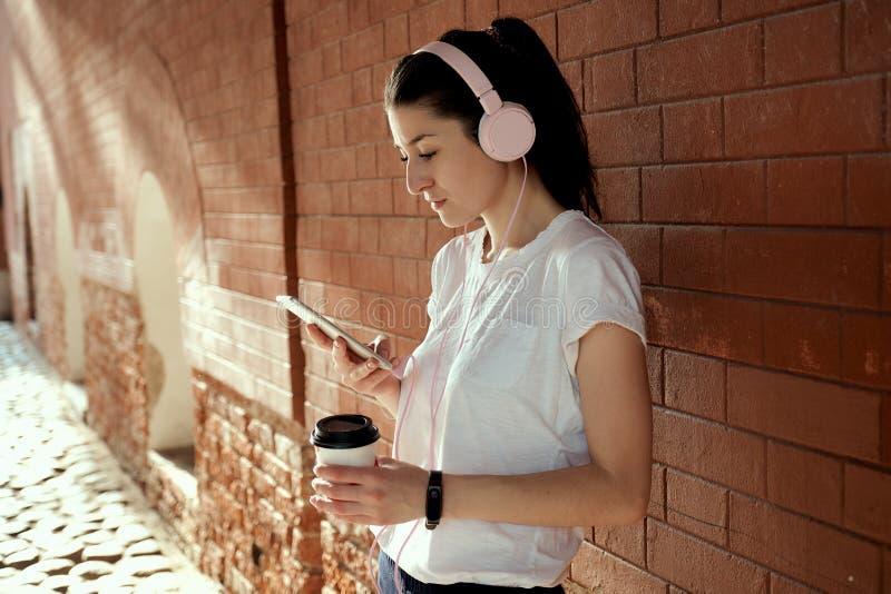 La donna abbastanza caucasica dei giovani con la tazza di caffè e dello Smart Phone in sue mani sta il muro di mattoni vicino sol fotografie stock libere da diritti